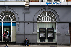 © Licensed to London News Pictures. 02/04/2020. London, UK. A woman wearing a face mask walks past a branch of Barclays Bank in Haringey, north London which is closed following coronavirus lockdown. The former Governor of the Bank of England, Lord King of Lothbury, has said that bank branches should reopen to ensure that businesses are able to access the emergency funding on offer from the Government. Photo credit: Dinendra Haria/LNP