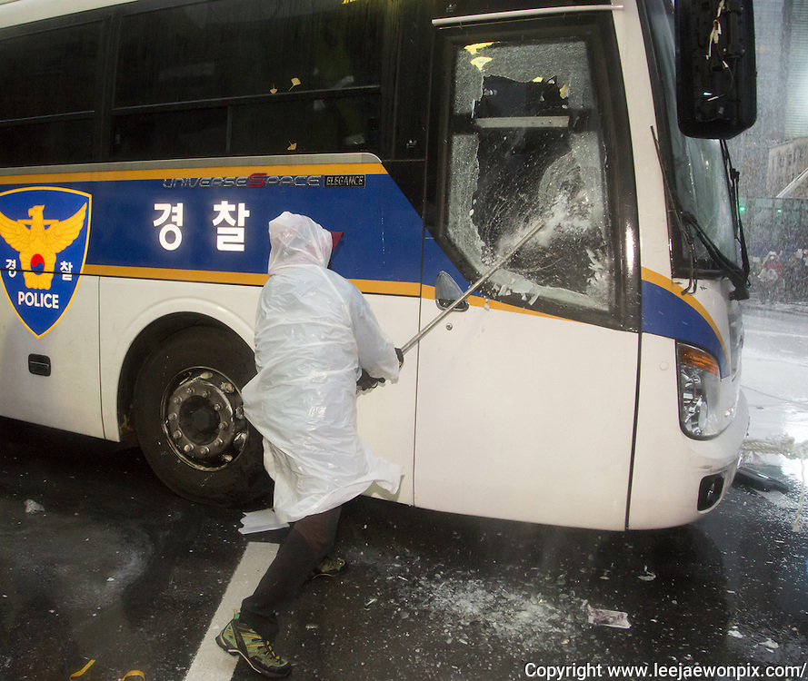 """A protester hits a police bus set as barriers by the police during an anti-government protest in central Seoul, South Korea, November 14, 2015. """"The People's Camp for Rising Up and Fighting"""", representing various groups of farmers, students, workers and the poor, demonstrated to oppose South Korean government's plans to change the labor market and monopolize the authorship of history textbooks. Policemen set up vehicle barriers and used water cannon to break up people. The organizer said 130,000 people participated in the demo, while the police said 68,000 attended. Photo by Lee Jae-Won"""
