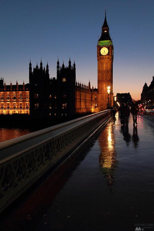 Big Ben reflected in Westminster Bridge after rain at sunset.