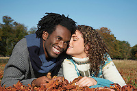 Couple lying in grass with autumn leaves