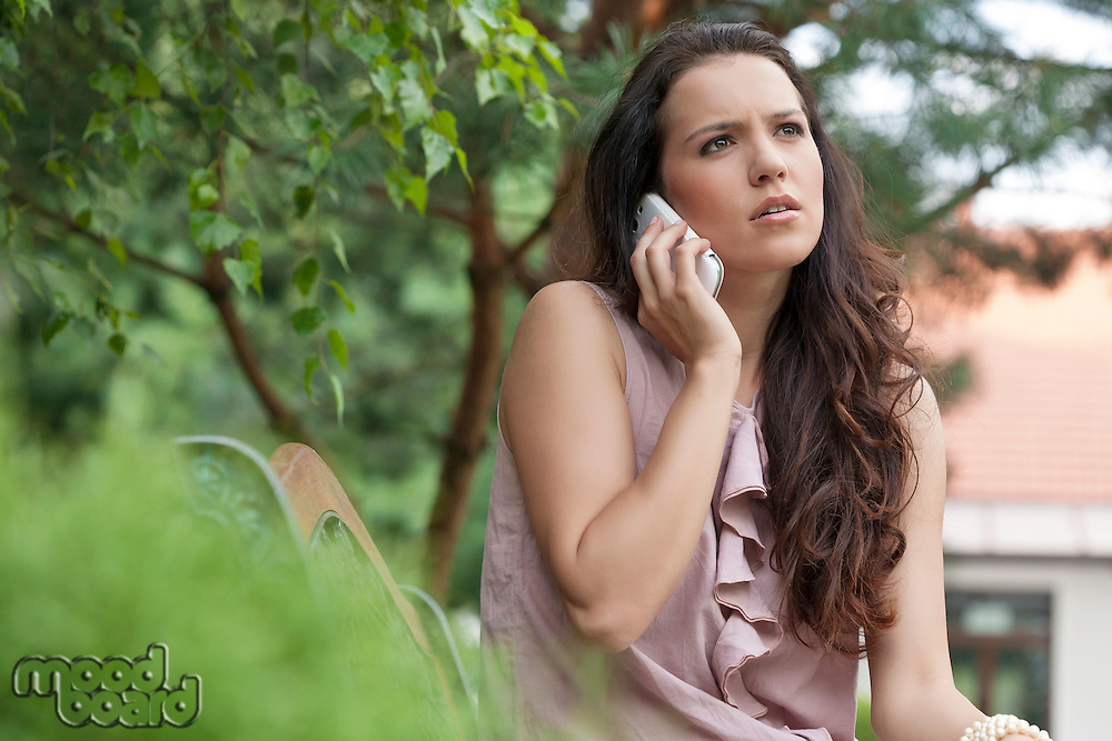Beautiful young woman looking away while on call at park