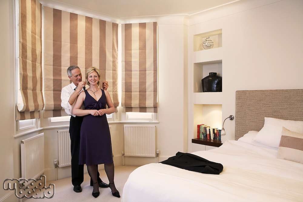 Middle-aged couple in bedroom man helping woman with necklace