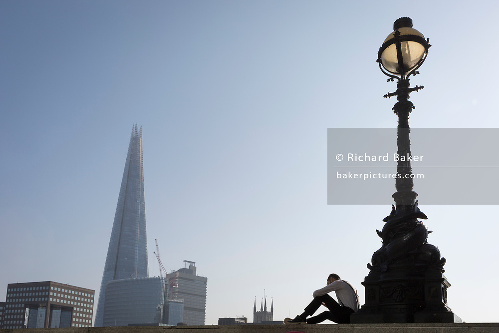 An office worker in the City of London - the capital's financial district - enjoys late summer temperatures on Hanseatic Walk that overlooks the Shard skyscraper on the Thames river, on 10th October 2018, in London, England.