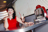 Retro woman in red dress in American diner