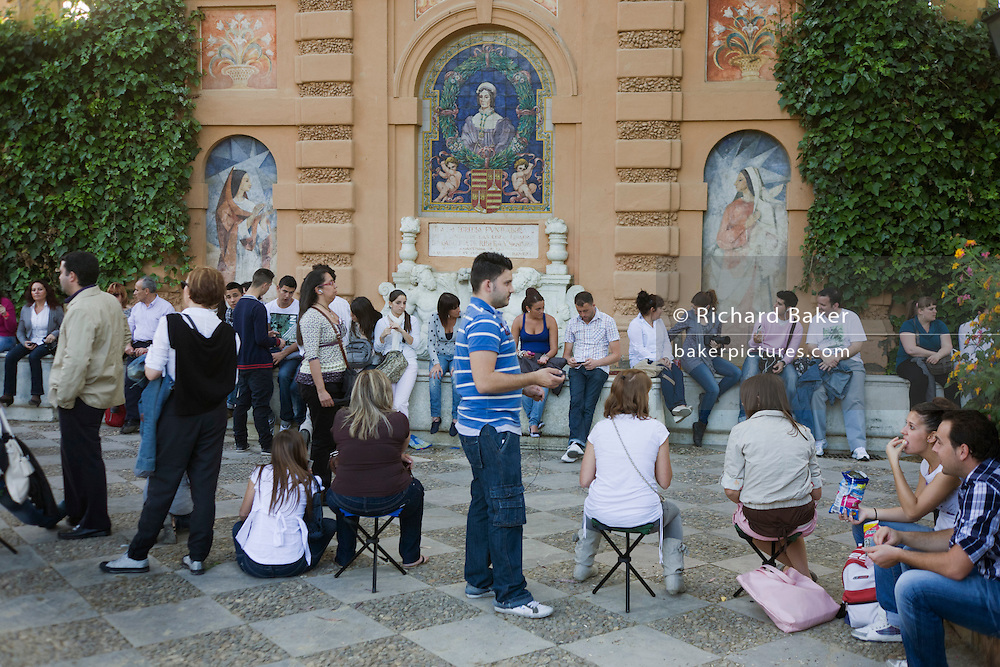 Devout Spaniards await an Easter procession in Jardines de Murillo during Semana Santa.