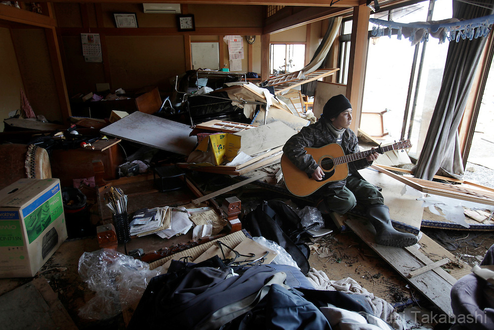 A man, surrounded by debris, plays a guitar in his house in MInamisanriku, Miyagi, Japan on March 31, 2011 after massive earthquake and tsunami hit northern Japan. More than 20,000 were killed by the disaster on March 11.<br /> Photo by Kuni Takahashi