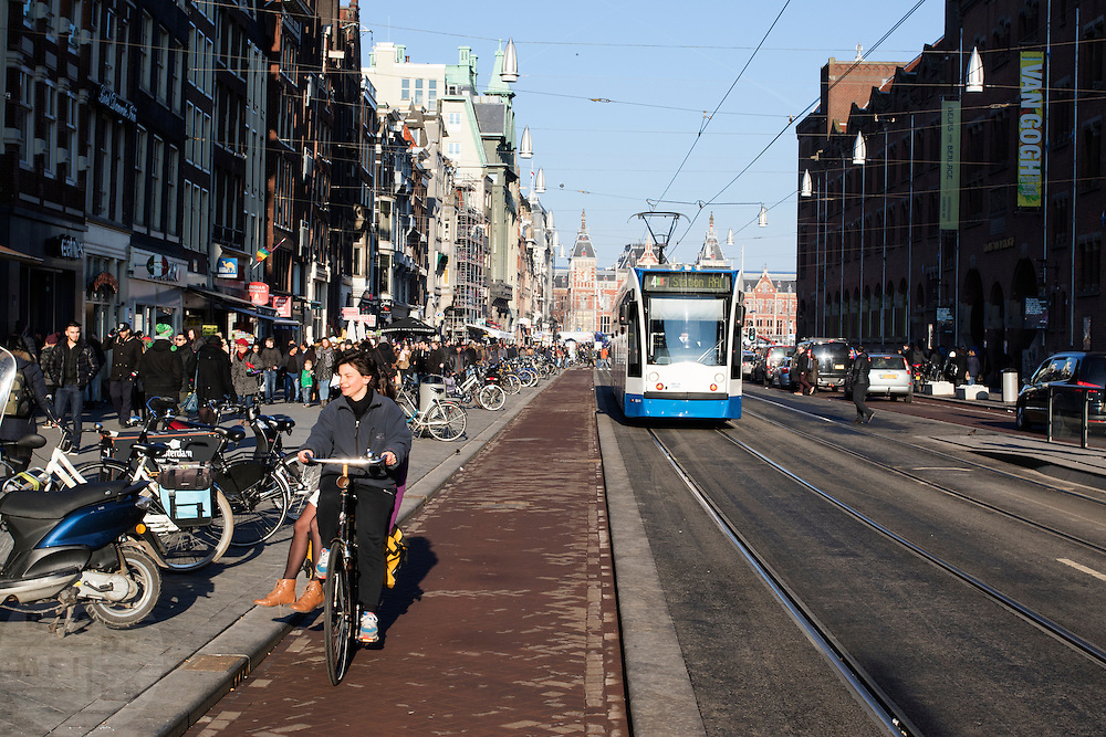In Amsterdam tijden twee vrouwen op een fiets op het fietspad terwijl een tram voorbij komt rijden. Het Damrak is onlangs opnieuw ingericht met een duidelijkere scheiding tussen fietsers, trams en auto's.<br /> <br /> In Amsterdam two women are riding on a bike at the Damrak while a tram is passing. The Damrak is newly redesigned with a clearer separation between cyclists, trams and cars.