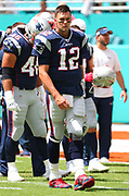 Sep 15, 2019; Miami Gardens, FL, USA;  New England Patriots quarterback Tom Brady (12) surveys the field before an NFL game between the Miami Dolphins and the New England Patriots at Hard Rock Stadium in Miami Gardens, FL. The Patriots beat the Dolphins 43-0. (Steve Jacobson/Image of Sport)