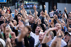 © Licensed to London News Pictures . 27/09/2018 . London , UK . Supporters of former EDL leader Tommy Robinson (real name Stephen Yaxley-Lennon ) gesture towards an upper floor window outside the Old Bailey , as Robinson faces a retrial for Contempt of Court following his actions outside Leeds Crown Court in May 2018 . Robinson was already serving a suspended sentence for the same offence when convicted in May and served time in jail as a consequence , but the newer conviction was quashed by the Court of Appeal and a retrial ordered . Photo credit: Joel Goodman/LNP