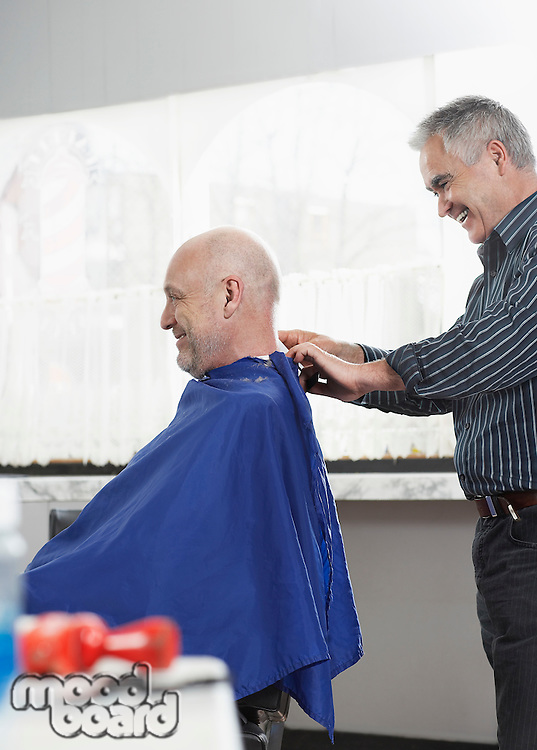Barber removing cape from man in barber shop