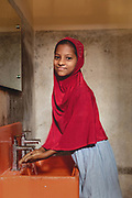 A girl washes her hands with clean water in a Splash sink