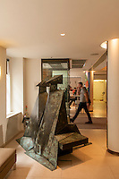 "Lynn Chadwick's sculpture ""Sitting couple on bench"" in Christie's King street lobby with Colin the doorman."