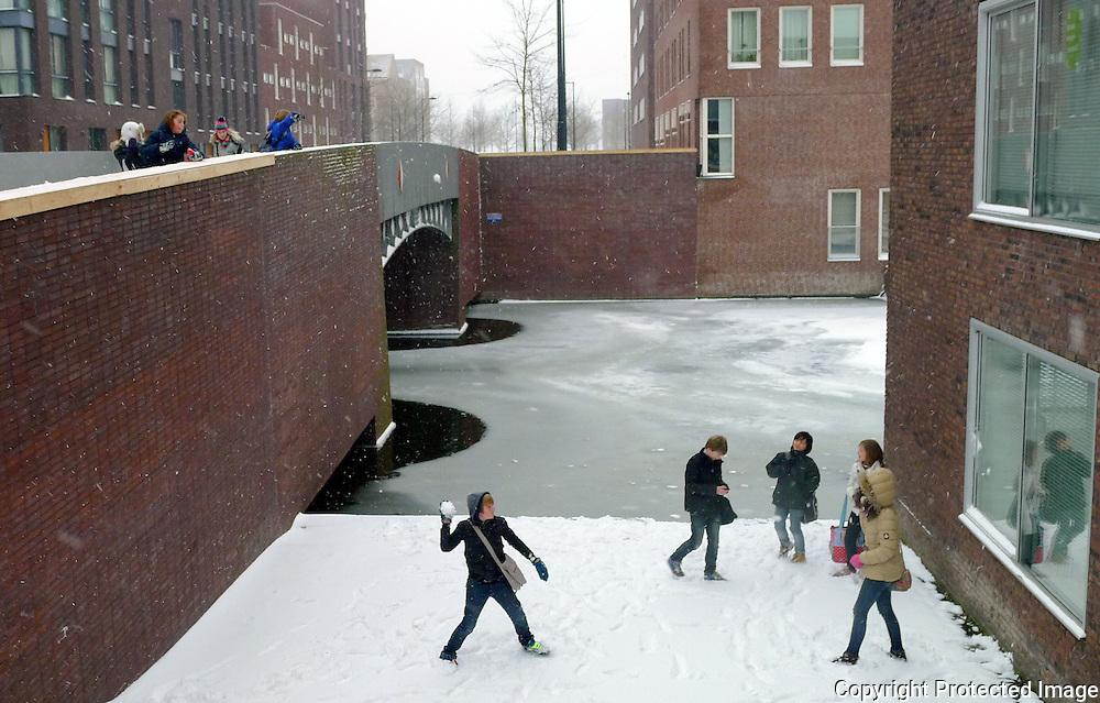 Nederland, Amsterdam, 21 januari 2013.Kinderen gooien met sneeuwballen in de Maria Austriastraat op IJburg..Kids throw snowballs to each other in the Maria Austriastraat on IJburg.