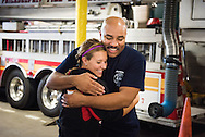 Darrian Doederlein of the 2014 Youth Corps pilot project receives a hug from Marc Howard, a firefighter at the Philadelphia Fire Department, as she and the Rev. Steven Schave, director of LCMS Urban & Inner-City Ministry (not pictured), visit a fire station near Shepherd of the City Lutheran Church on Tuesday, August 12, 2014, in Philadelphia, Pa. They were part of a Gospel Seeds session held during the event. LCMS Communications/Erik M. Lunsford