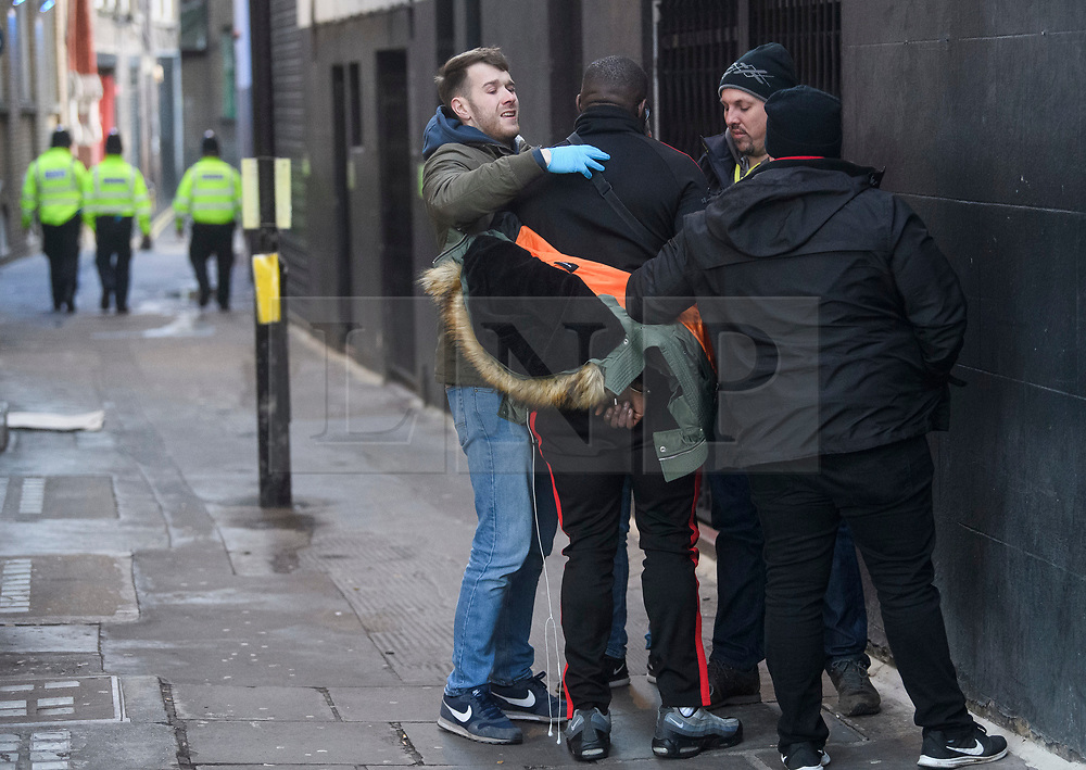 © Licensed to London News Pictures. 17/12/2018. London, UK.  Plain clothed police officers, working with the facial recognition team, detain a man and put him in handcuffs, while testing the software.. Members of the Metropolitan police trial facial recognition technology on members of the public in central London. The surveillance software is being used overtly with a uniformed presence. Privacy campaigners have expressed concerns about the use of the technology. Photo credit: Ben Cawthra/LNP