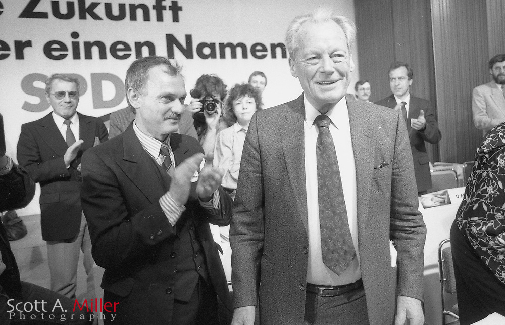 Leipzig East Germany; Feb 1990: Ibrahim Böhme (left), first chairman of the East German Social Democrats (1989-1990) applauds as Willy Brandt, former West German Chancellor (1969-1974) , and leader of the Social Democratic Party of Germany (SPD) from 1964-1987 is introduced at a rally..©1990 Scott A. Miller