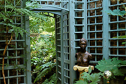 Shady corner with large mirror framed by trellis. Sculpture on plinth by Camilla Shivarg.