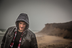 rugged man in a hooded coat on the beach in Montauk, NY