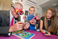 At the opening of his new Optometrists in Preston on Saturday  Mike Broadhurst times Lauren and Adam Powell as they try their hand at a simple jigsaw puzzle while wearing special goggles to simulate visual impairments, to demonstrate the importance of eye checks for children. ..18 August 2012.Image © Paul David Drabble