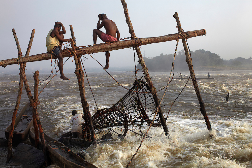 Fishermen check their baskets at Wagenia Falls (or Boyoma Falls) in the middle of the Congo River, near Kisangani, DR Congo. Most of the wooden frames are built near the river's edge but some of the fishermen build frames in the very center of the river were the flow is greatest as they believe this is where the strongest, and biggest, fish live.