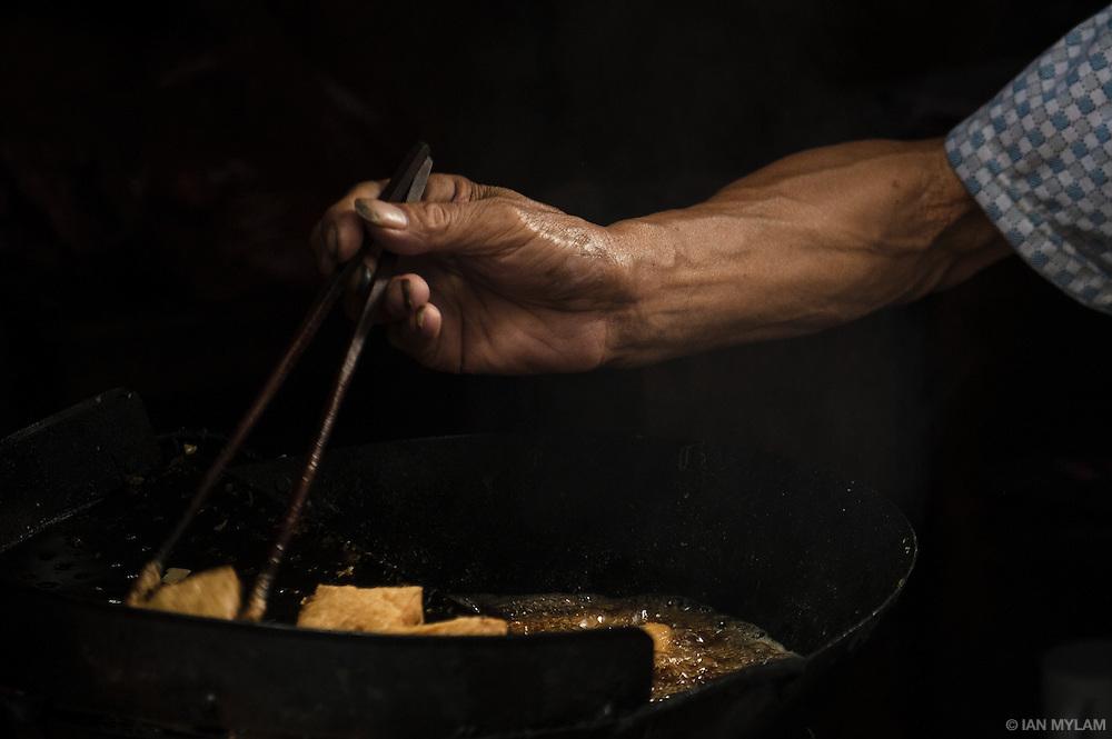 A street vendor prepares food in a wok, Xitang, Zhejiang, China
