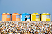 © Licensed to London News Pictures. 14/04/2015. Seaford, UK. A woman walks past colourful beach huts. People in the early morning sea mist and sunshine in Seaford today 14th April 2015. Today is expected to be a very warm day across Britain. . . Photo credit : Stephen Simpson/LNP