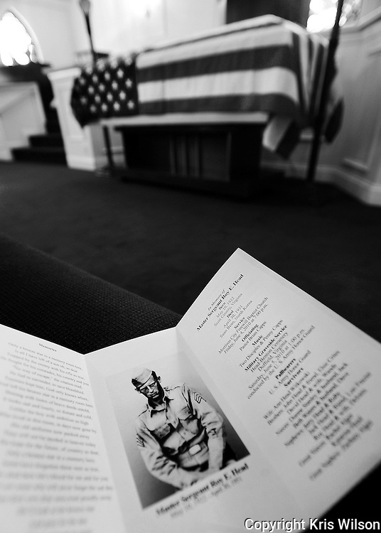 A memorial card for Master Sgt. Roy E. Head rests on an empty pew in the West Chapel at Scott County Funeral Home where the remains of the former Korean War P.O.W. lie in repose prior to burial. Photo by Kris Wilson.