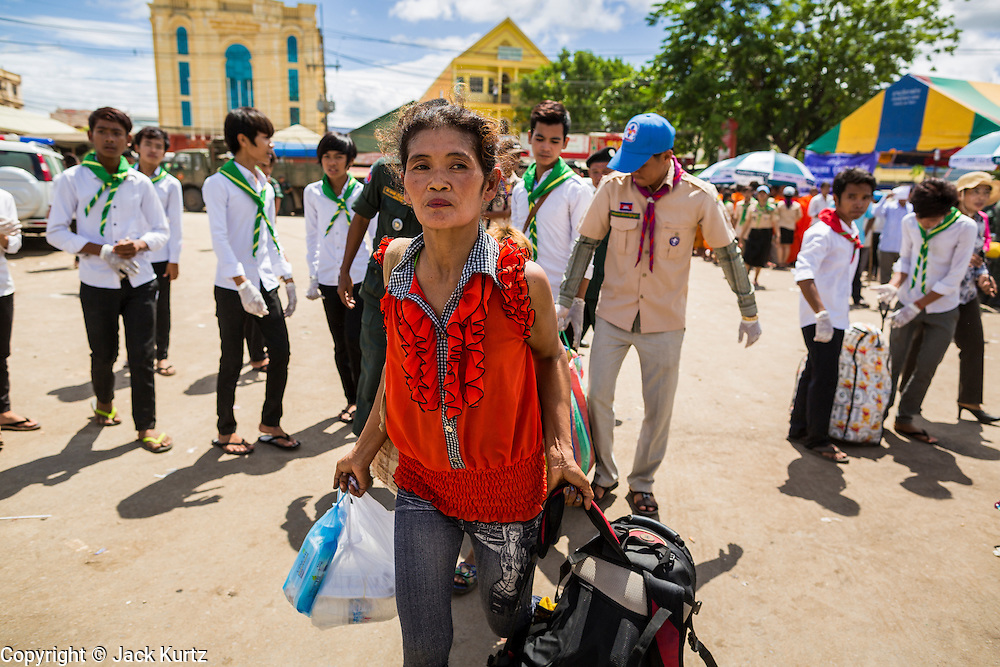 16 JUNE 2014 - POIPET, CAMBODIA: A Cambodian migrant carries her belongings through Poipet, Cambodia after he returned to Cambodia from Thailand. More than 150,000 Cambodian migrant workers and their families have left Thailand since June 12. The exodus started when rumors circulated in the Cambodian migrant community that the Thai junta was going to crack down on undocumented workers. About 40,000 Cambodians were expected to return to Cambodia today. The mass exodus has stressed resources on both sides of the Thai/Cambodian border. The Cambodian town of Poipet has been over run with returning migrants. On the Thai side, in Aranyaprathet, the bus and train station has been flooded with Cambodians taking all of their possessions back to Cambodia.  PHOTO BY JACK KURTZ