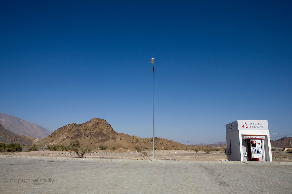 Between Muscat and Nizwa, Sultanate of Oman. .February 1st 2009..An ATM on the road in the middle of the desert