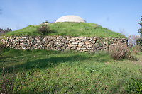 view from outside of Etrurian grave in Italy with dome on small hill, the tomb is below with corridors and pillar below dome