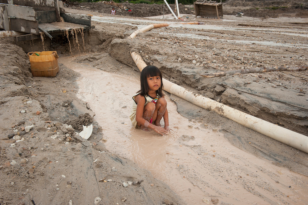 The hidden side of high tech smartphones. Child sits in devastated landscape created by her family members, who are miners in a huge illegal tin mine in Batako, Tunghin,  a few meters from the village they live in. Bangka Island (Indonesia) is devastated by a deadly tin rush, a direct consequence of the success of smartphones and tablets like iPhones and iPads from Apple or Samsung. The demand and price for tin has increased due to its use in smart phones and tablets.<br /> <br /> Le c&ocirc;t&eacute; cach&eacute; du succ&egrave;s des smartphones. Enfant dans un paysage d&eacute;vast&eacute;, cr&eacute;&eacute; par les membres de sa famille, mineurs dans une immense mine d'&eacute;tain ill&eacute;gale &agrave; Batako, Tunghin, &agrave; quelques m&egrave;tres du village. L'&icirc;le de Bangka (Indon&eacute;sie) est d&eacute;vast&eacute;e par des mines d'&eacute;tain sauvages, une cons&eacute;quence directe du succ&egrave;s des smartphones et tablettes comme les iPhones et les iPads d'Apple ou Samsung. La demande de l'&eacute;tain a explos&eacute; &agrave; cause de son utilisation dans les smartphones et tablettes.