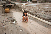 The hidden side of high tech smartphones. Child sits in devastated landscape created by her family members, who are miners in a huge illegal tin mine in Batako, Tunghin,  a few meters from the village they live in. Bangka Island (Indonesia) is devastated by a deadly tin rush, a direct consequence of the success of smartphones and tablets like iPhones and iPads from Apple or Samsung. The demand and price for tin has increased due to its use in smart phones and tablets.<br /> <br /> Le côté caché du succès des smartphones. Enfant dans un paysage dévasté, créé par les membres de sa famille, mineurs dans une immense mine d'étain illégale à Batako, Tunghin, à quelques mètres du village. L'île de Bangka (Indonésie) est dévastée par des mines d'étain sauvages, une conséquence directe du succès des smartphones et tablettes comme les iPhones et les iPads d'Apple ou Samsung. La demande de l'étain a explosé à cause de son utilisation dans les smartphones et tablettes.