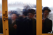 A group of Orthodox Jewish boys in fancy dress collecting for charity try and visit a wealthy man of the area; some houses are so popular they have to wait to get in and they have bouncers on the door. Purim is one of the most entertaining Jewish holidays.  It commemorates the time when the Jewish people living in Persia were saved from extermination from a massacre by Haman. Due to the courage of a young Jewish woman called Esther. It is customary to hold carnival-like celebrations on Purim, and for groups of men to go round on the back of lorries and in open top buses visiting local wealthy men, collecting for their charity.