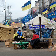 December 18, 2013 - Kiev, Ukraine: Pro-EU demonstrators, one holding a sign saying 'together we are powerful, we won't be overcome' sit in Independence Square.<br /> On the night of 21 November 2013, a wave of demonstrations and civil unrest began in Ukraine, when spontaneous protests erupted in the capital of Kiev as a response to the government&rsquo;s suspension of the preparations for signing an association and free trade agreement with the European Union. Anti-government protesters occupied Independence Square, also known as Maidan, demanding the resignation of President Viktor Yanukovych and accusing him of refusing the planned trade and political pact with the EU in favor of closer ties with Russia.<br /> After a days of demonstrations, an increasing number of people joined the protests. As a responses to a police crackdown on November 30, half a million people took the square. The protests are ongoing despite a heavy police presence in the city, regular sub-zero temperatures, and snow. (Paulo Nunes dos Santos/Polaris)