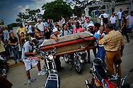 Family and friends make homage to a motorizado shot down in the La Pastora (The Shepherd) slum in Caracas, Venezuela by resting his casket on motorcycles and revving their engines while other motorizados make a series of laps around the cemetery at high speed, revving their engines as well, and occasionally riding on one wheel. Although a great percentage of motorizados work honestly, the profession is often criminalized because of its association with delinquent behavior. The agility of motorcycles makes them the preferred get-away vehicle for criminals involved in robberies, kidnappings and murders. Motorizados often find themselves victims of criminal activity as well, motorcycle theft is rampant in Caracas and newspapers report murders of motorizados weekly.