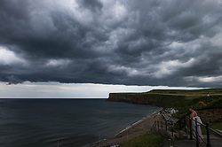 © Licensed to London News Pictures.05/07/15<br /> Saltburn by the Sea, UK. <br /> <br /> A woman stands looking at Huntcliff as storm clouds pass overhead on the coastline at Saltburn by the Sea. <br /> <br /> Photo credit : Ian Forsyth/LNP