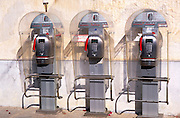 Three public telephones against wall, Sicily, Italy