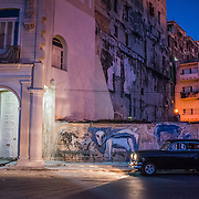 Before the sunrise, Havana wakes up. A classic car waits for its passenger as its headlights illuminate an arch and doorway.