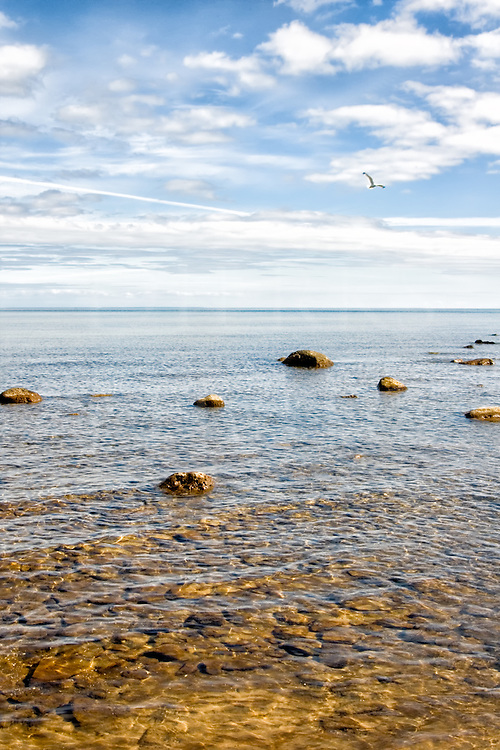 Scenic rocky shallow water at the edge of a tranquil and serene Lake Michigan in the Upper Peninsula.