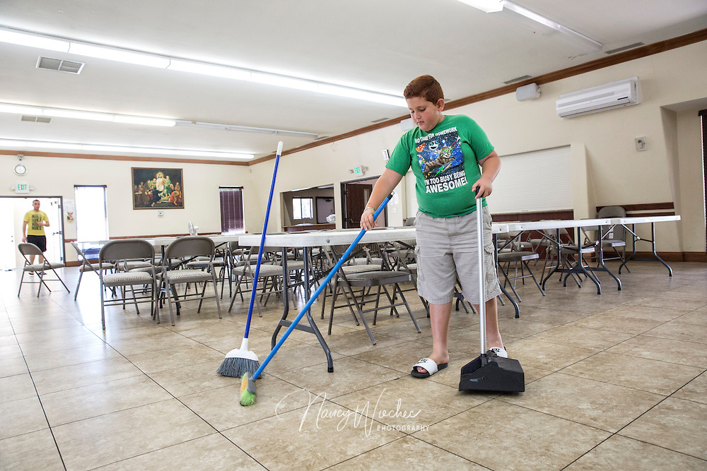 Domunik Shamoun, 11, helps clean the hall following a Bingo game at St. Michael Chaldean Catholic Church in El Cajon, Calif., Aug. 14, 2015. Domunik came to the U.S. from Iraq in 2008. (Nancy Wiechec for ONE magazine)