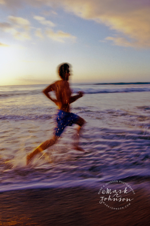 Man running along beach at sunset, Polihale, Kauai, Hawaii
