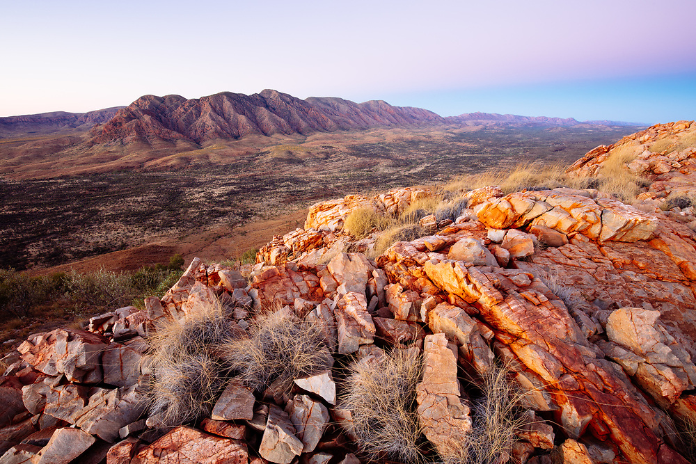 Ancient rocks of the Heavitree Range in the foreground with the Alice Valley seperating Mount Giles in the distance. Larapinta Trail, Tjoritja/West MacDonnell National Park.