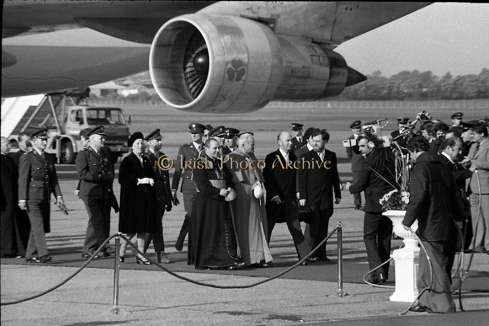Pope John-Paul II visits Ireland..1979..29.09.1979..09.29.1979..29th September 1979..Today marked the historic arrival of Pope John-Paul II to Ireland. He is here on a three day visit to the country with a packed itinerary. He will celebrate mass today at a specially built altar in the Phoenix Park in Dublin. From Dublin he will travel to Drogheda by cavalcade. On the 30th he will host a youth rally in Galway and on the 1st Oct he will host a mass in Limerick prior to his departure from Shannon Airport to the U.S..Image of John-Paul II accompanied by Cardinal Tomás Ó Fiach and President Hillery walking the red carpet to the podium.