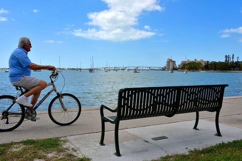 Man Riding Bicycle along Sarasota Bay in Sarasota, Florida<br /> This elderly gentleman is enjoying his bicycle ride along Bayfront Drive, a waterfront boulevard along Sarasota Bay.  He is one of the 30% of people 65 and over who are living their retirement in Sarasota County, Florida.  In the background is the Golden Gate Point peninsula. The bridge is the John Ringling Causeway.