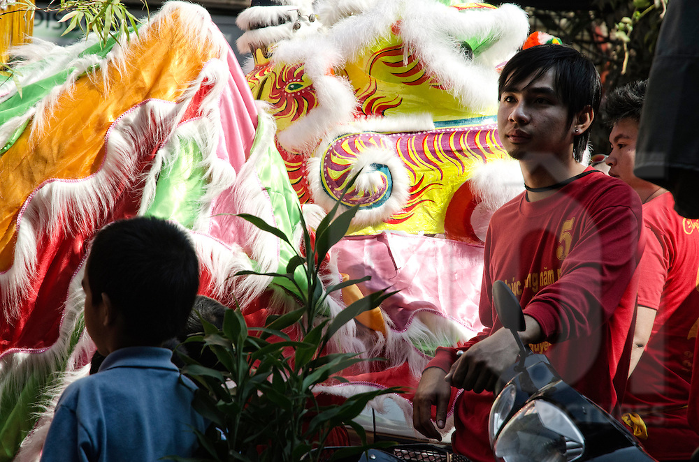 Tet festival (Vietnamese happy new year or chinese new year) in Vientiane, Laos, Asia.  Young teenagers stand close to a cardboard decorated lion head.