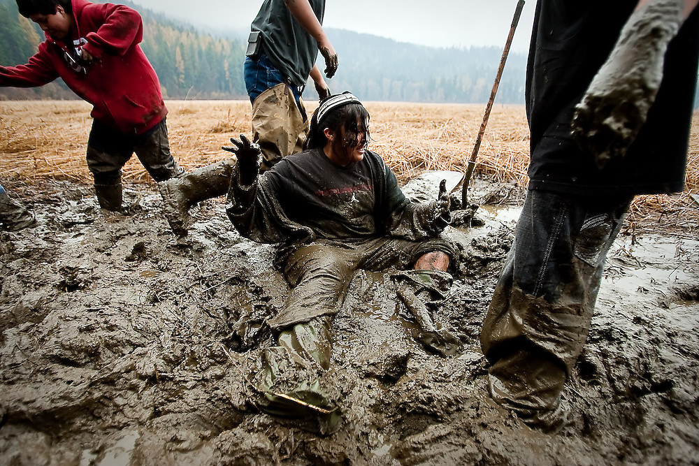 JEROME A. POLLOS/Press..Kyra Antone, 13, sits in the cold mud after falling when her waders became stuck while digging for water potatoes.