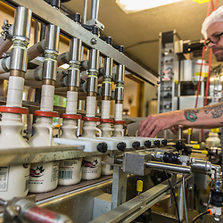 Owner Fabian LaRiviere works the bottling conveyer at Maine Maple Products in Madison, Maine. The majority of the syrup bottled here is harvested in Big Six Township, Maine.