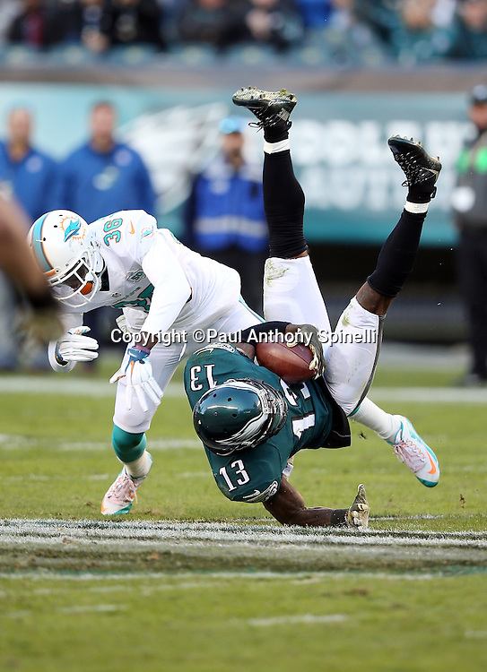 Philadelphia Eagles wide receiver Josh Huff (13) gets upended by Miami Dolphins defensive back Tony Lippett (36) after catching a fourth quarter pass for a gain of 16 yards and a first down during the 2015 week 10 regular season NFL football game against the Miami Dolphins on Sunday, Nov. 15, 2015 in Philadelphia. The Dolphins won the game 20-19. (©Paul Anthony Spinelli)