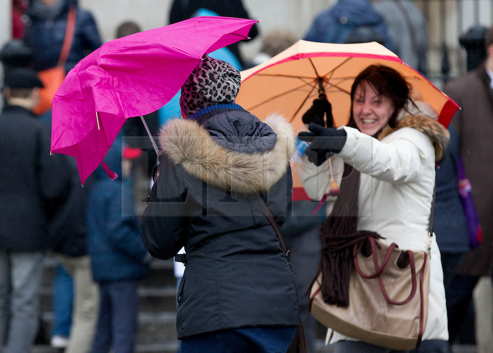 © Licensed to London News Pictures. 23/12/2013. London, UK. A tourist laughs at a friend vainly sheltering beneath a broken umbrella outside the National Gallery in London today (23/12/2013). Weather warnings were yesterday issued for the United Kingdom predicting severe wind and rain that may affect holiday travel. Photo credit: Matt Cetti-Roberts/LNP