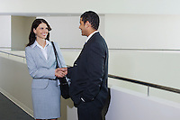 Business couple shaking hands in office hallway
